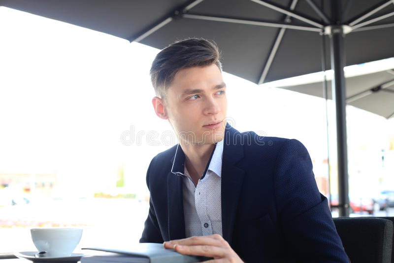 Retrato de um homem de negócios seguro que senta-se no banco e no café bebendo fora imagem de stock royalty free