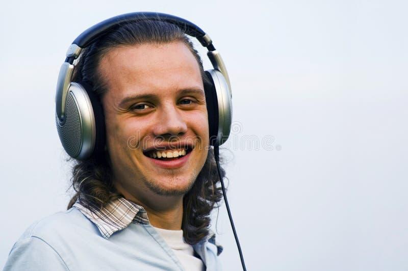 Retrato de um homem de sorriso com fones de ouvido fotografia de stock royalty free