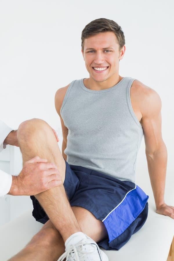 Retrato de um homem de sorriso que obtém seu pé examinado imagem de stock royalty free
