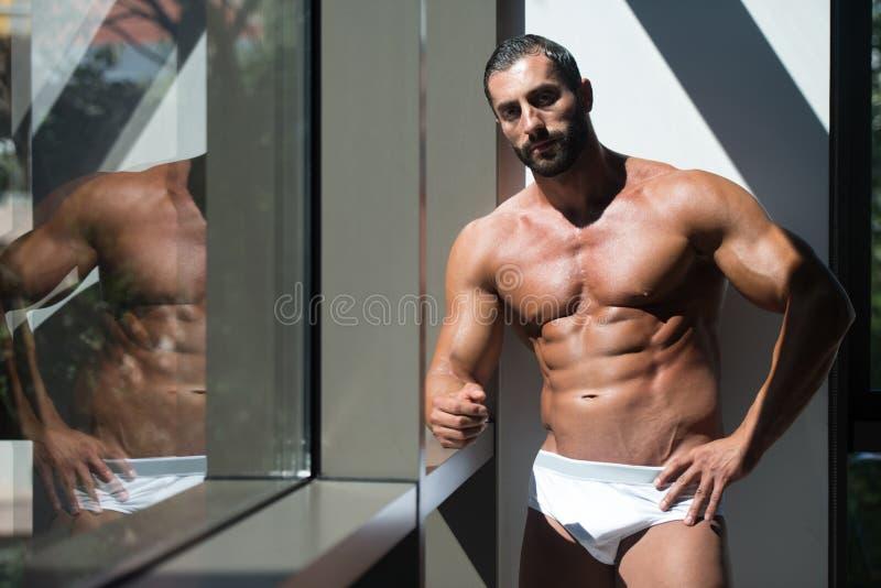 Retrato de um homem descamisado muscular no roupa interior fotografia de stock