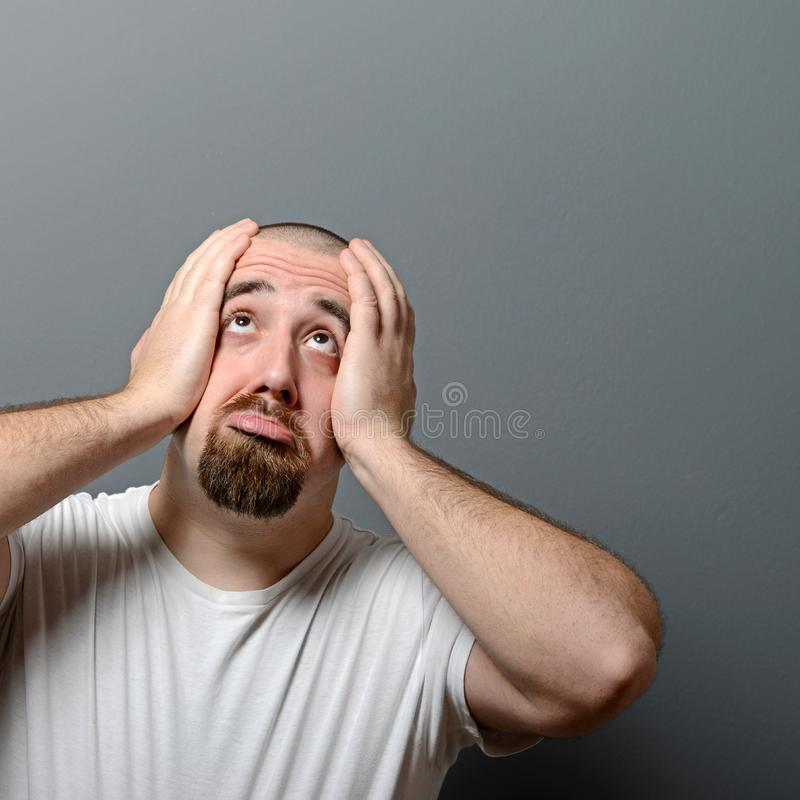 Retrato de um homem desesperado em choque contra o fundo cinzento fotos de stock