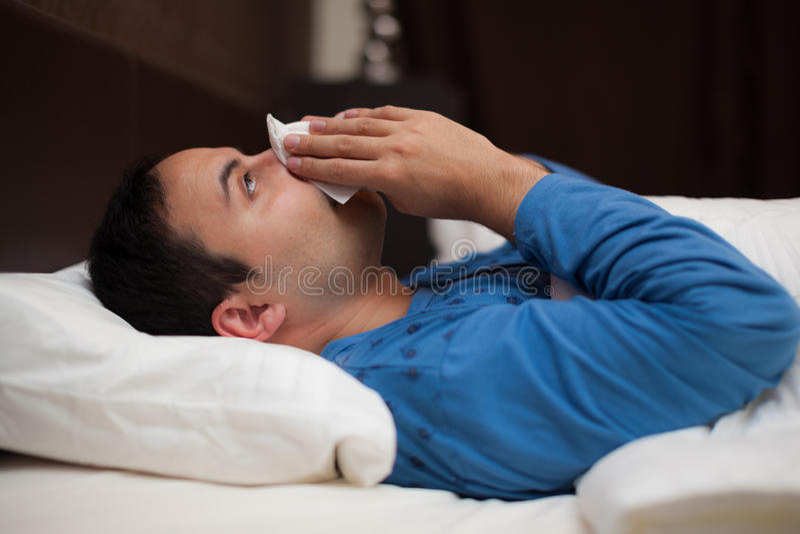 Retrato de um homem doente que funde seu nariz fotografia de stock