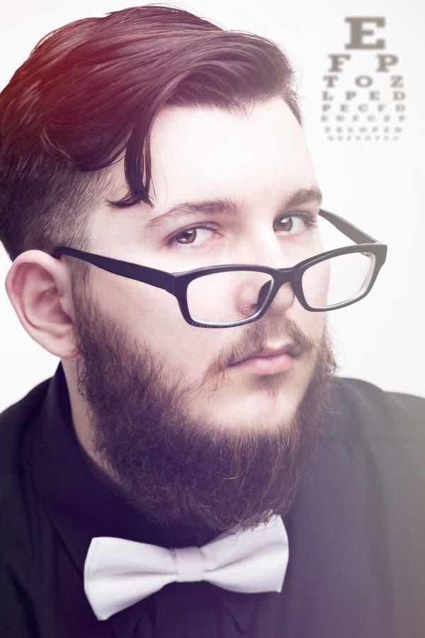 Retrato de um homem elegante novo do moderno na camisa e em monóculos pretos no fundo branco fotos de stock