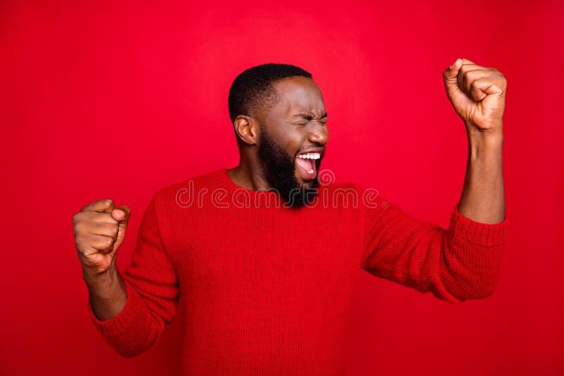 Retrato de um homem encantado, gritando seus punhos, comemore a festa de ano novo usando suéter trendy isolado sobre fotos de stock