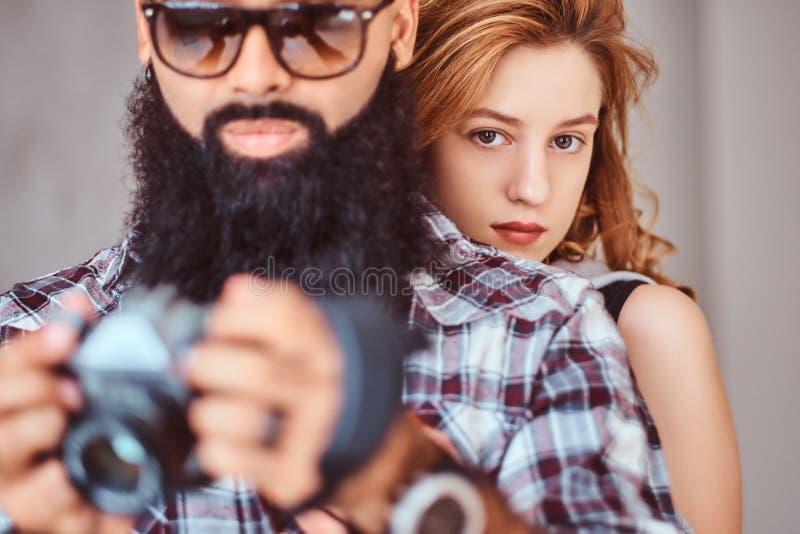 Retrato de um homem farpado árabe que guardam uma câmera e de sua amiga bonita do ruivo foto de stock