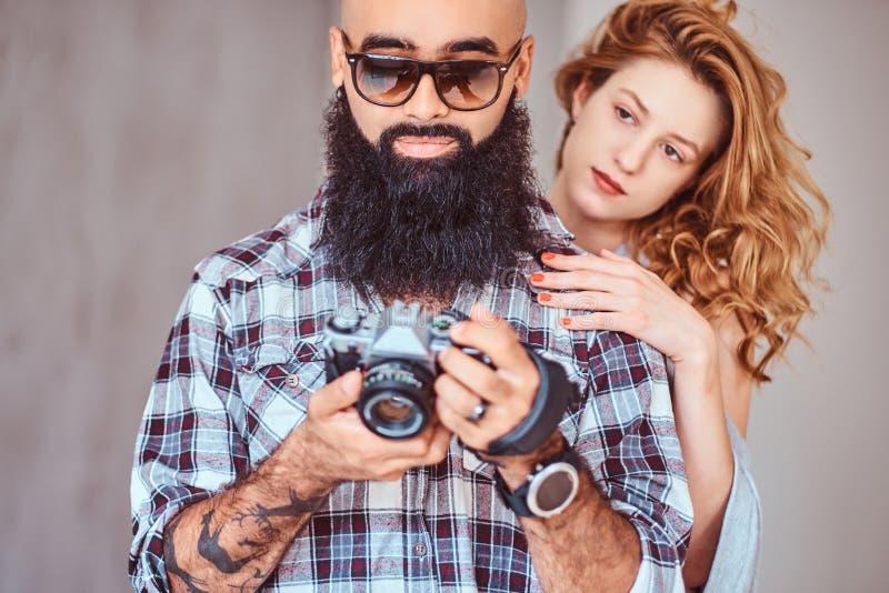 Retrato de um homem farpado árabe que guardam uma câmera e de sua amiga bonita do ruivo imagens de stock royalty free