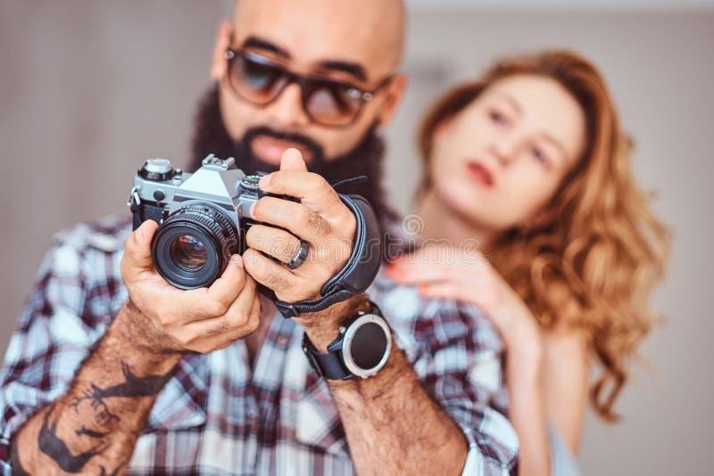 Retrato de um homem farpado árabe que guardam uma câmera e de sua amiga bonita do ruivo imagens de stock