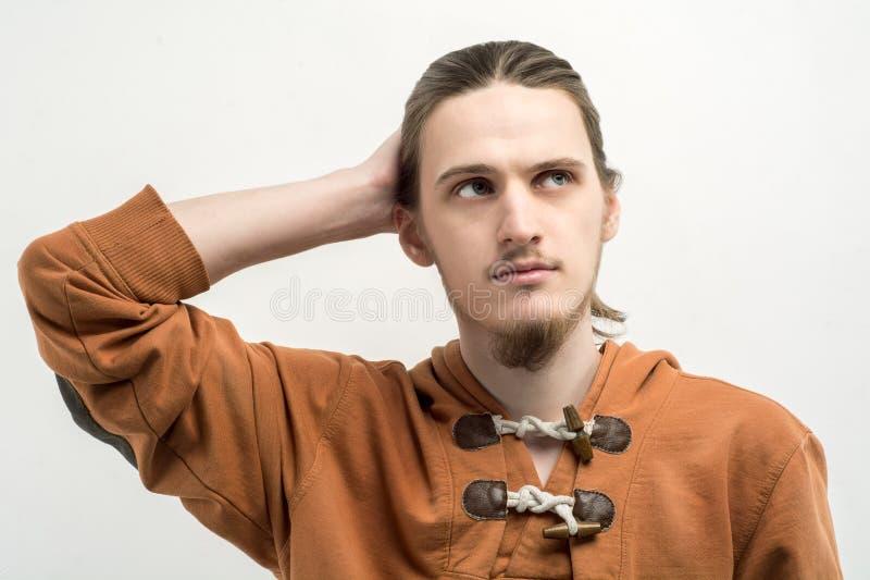 Retrato de um homem farpado considerável novo confundido com sua mão em sua cabeça que olha acima contra o fundo branco imagem de stock royalty free