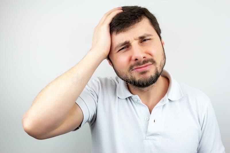Retrato de um homem farpado considerável que guarda sua cabeça com sua mão e que sofre da dor de cabeça imagem de stock royalty free