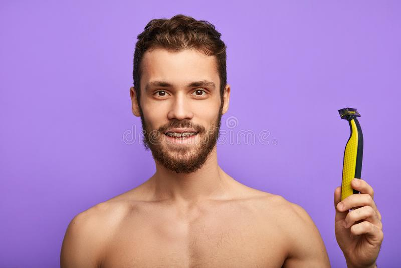 Retrato de um homem farpado descamisado positivo alegre que anuncia uma lâmina nova imagem de stock royalty free