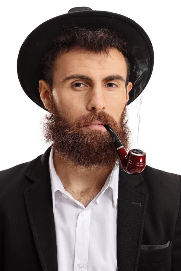 Retrato de um homem farpado que fuma uma tubulação fotos de stock
