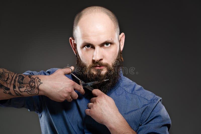 Retrato de um homem farpado que prepara sua barba com tesouras foto de stock royalty free