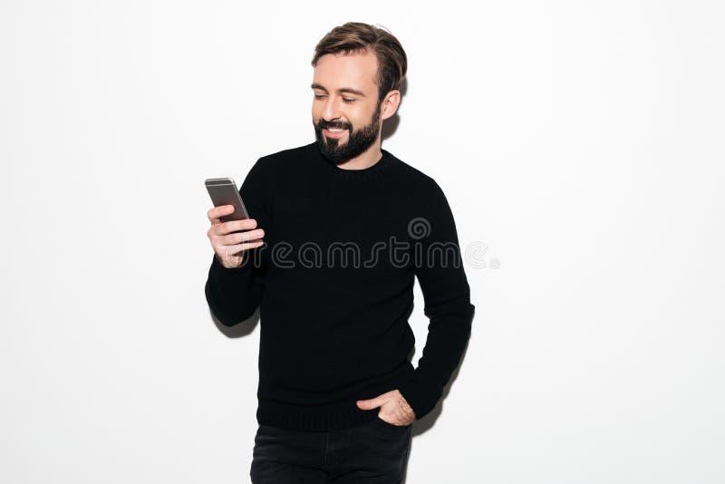 Retrato de um homem farpado de sorriso que texting no telefone celular fotografia de stock