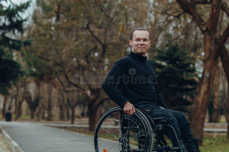 Retrato de um homem feliz em uma cadeira de rodas em um parque foto de stock