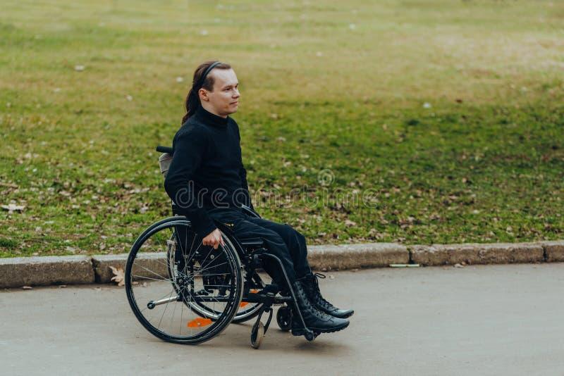 Retrato de um homem feliz em uma cadeira de rodas em um parque fotografia de stock