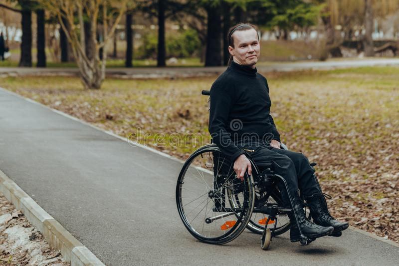 Retrato de um homem feliz em uma cadeira de rodas em um parque imagens de stock