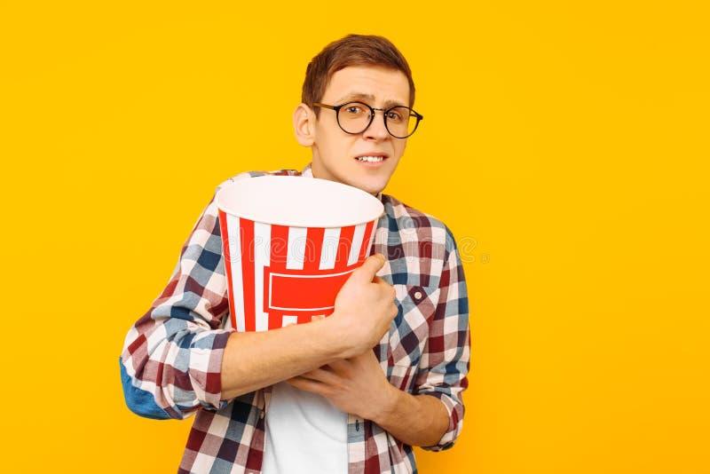Retrato de um homem feliz em vidros transparentes com uma cubeta da pipoca, afiada em olhar um filme, em um fundo amarelo fotografia de stock