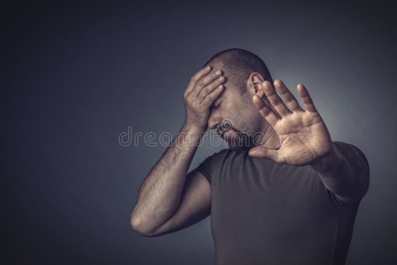 Retrato de um homem forçado com seus olhos fechados e sua mão em sua testa foto de stock royalty free