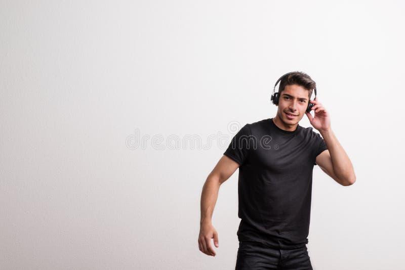 Retrato de um homem latino-americano novo alegre com fones de ouvido em um estúdio Copie o espaço fotografia de stock royalty free