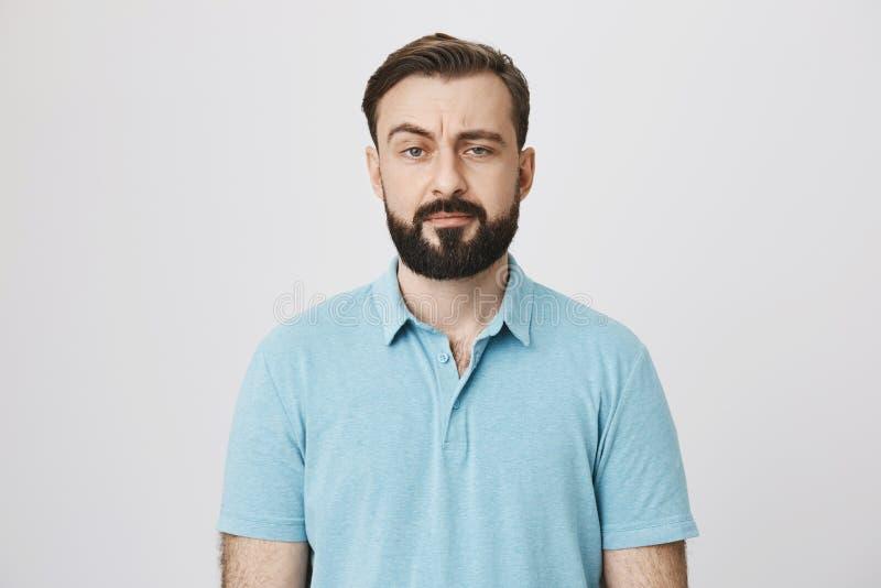 Retrato de um homem maduro com uma barba e um bigode que olham suspeitos A pessoa levanta sua sobrancelha e não faz realmente imagem de stock