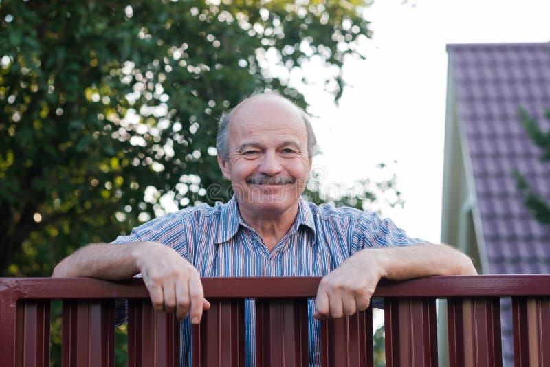 Retrato de um homem maduro considerável feliz que está de inclinação na cerca vermelha do metal fotos de stock royalty free