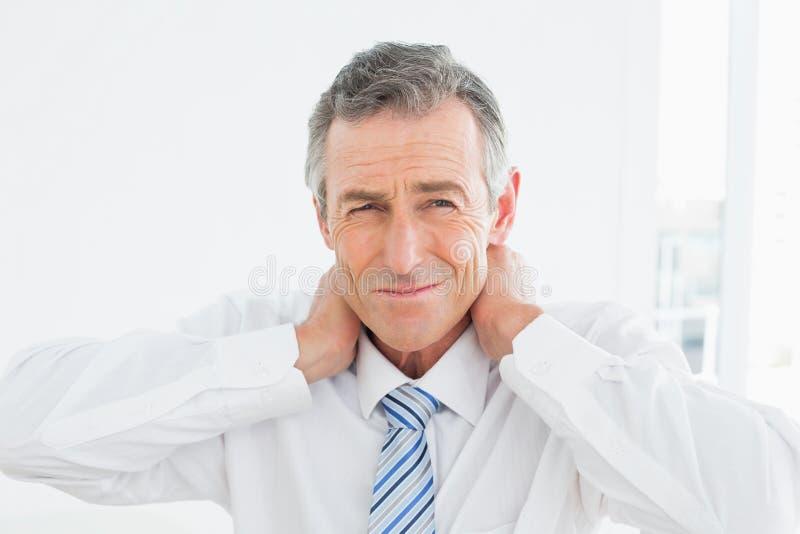 Retrato de um homem maduro que sofre da dor de pescoço fotos de stock