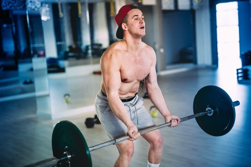 Retrato de um homem muscular, exercício com o barbell na instalação de formação, no gym fotos de stock