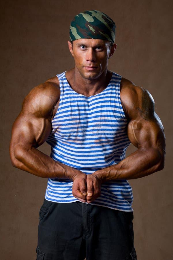 Retrato de um homem muscular forte em uma camisa listrada fotografia de stock