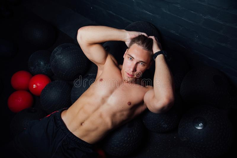 Retrato de um homem muscular que descansa e que encontra-se no assoalho no gym da aptidão foto de stock