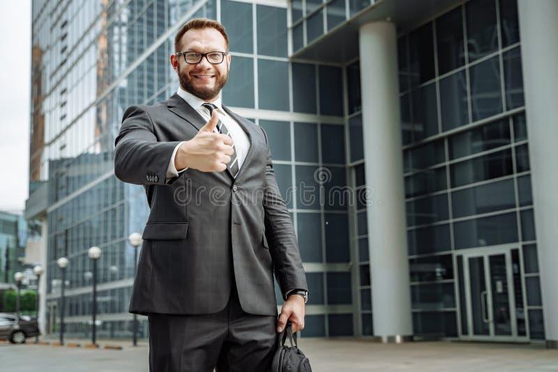 Retrato de um homem de negócio feliz que mostra seu polegar acima no fundo do centro de negócios fotografia de stock royalty free