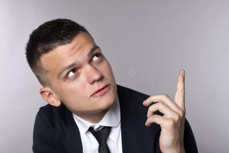 Retrato de um homem de negócio novo que tem a ideia e que aponta o dedo acima do fundo cinzento foto de stock royalty free