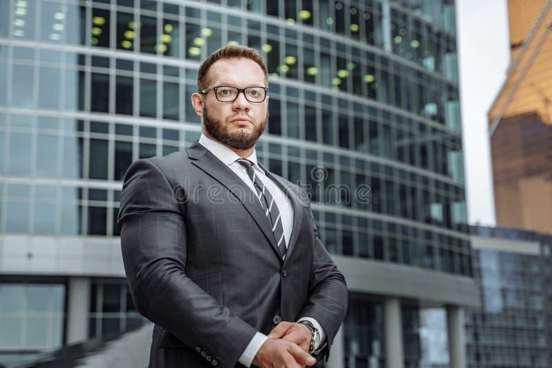 Retrato de um homem de negócio sério em um terno e de vidros no fundo de um prédio de escritórios fotos de stock royalty free