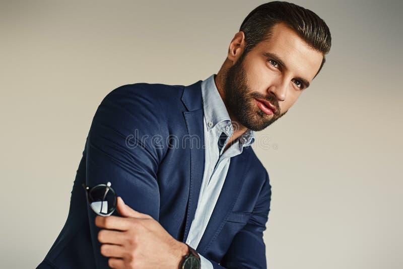 Retrato de um homem de negócios considerável e farpado 'sexy' na posição elegante do terno no escritório imagens de stock