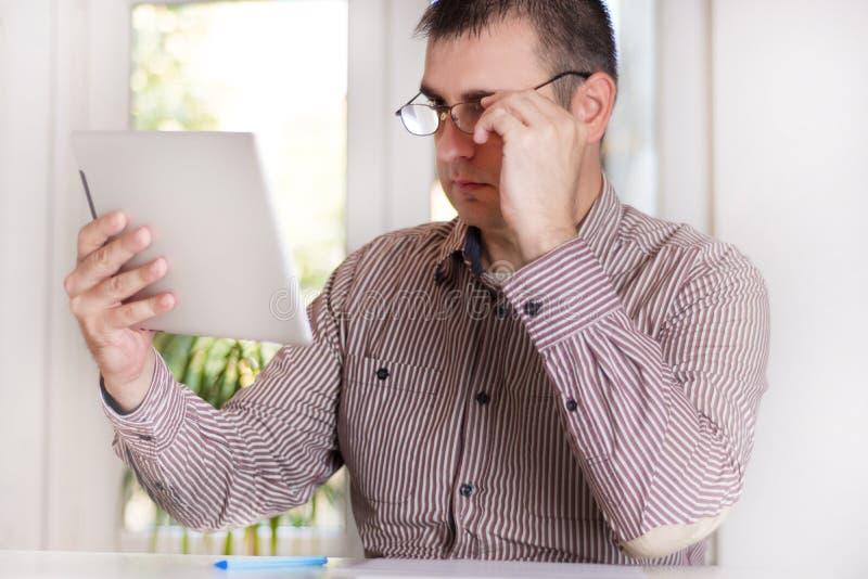 Retrato de um homem de negócios novo considerável que trabalha na tabuleta digital fotos de stock royalty free
