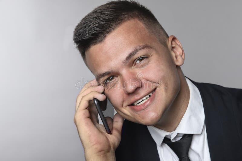 Retrato de um homem de negócios novo elegante de sorriso que usa o telefone celular imagens de stock