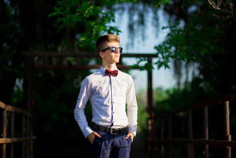 Retrato de um homem de negócios novo que veste uma camisa branca e óculos de sol O homem seguro faz planos foto de stock