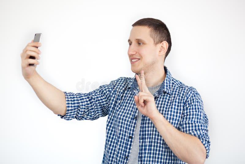 Retrato de um homem novo atrativo que toma um selfie ao estar e ao apontar o dedo isolado sobre o fundo branco Foto da foto de stock