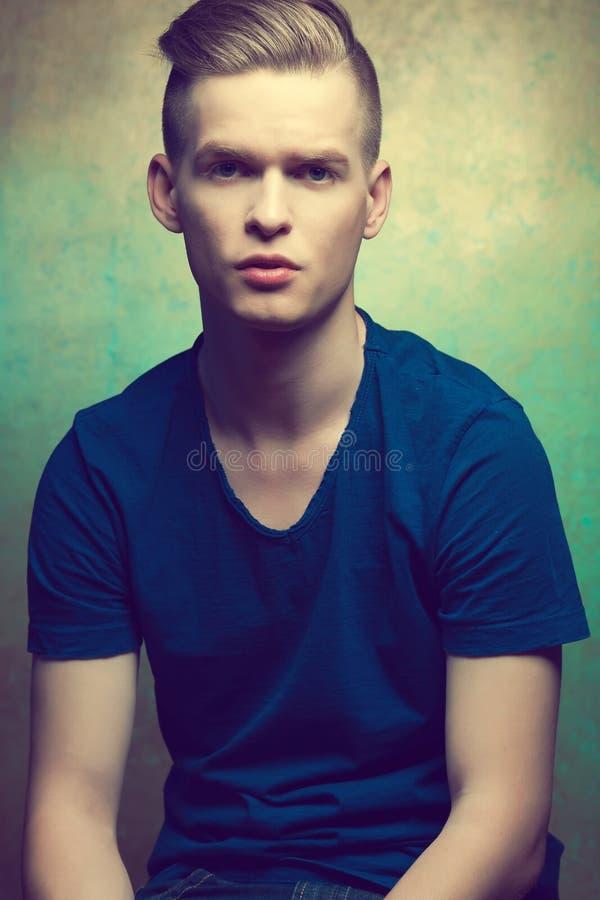 Retrato de um homem novo com a cara muito considerável em t ocasional azul fotos de stock