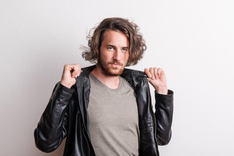 Retrato de um homem novo com revestimento preto em um estúdio fotografia de stock royalty free