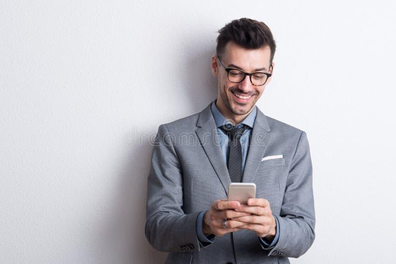 Retrato de um homem novo com smartphone em um estúdio, envio de mensagem de texto imagens de stock