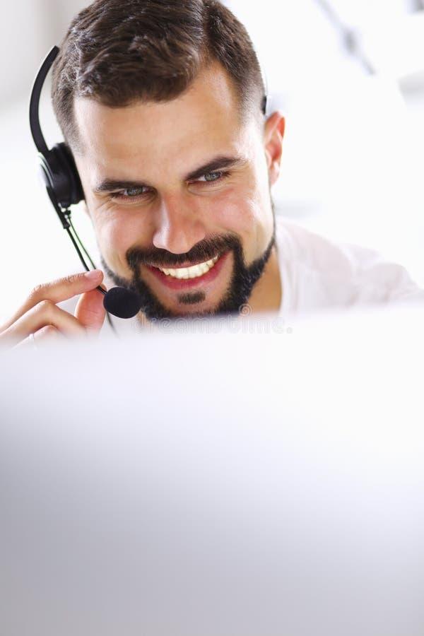 Retrato de um homem novo com uns auriculares na frente de um laptop fotografia de stock royalty free