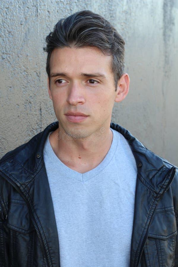 Retrato de um homem novo considerável da forma que inclina-se em uma parede cinzenta ao olhar longe da câmera imagem de stock