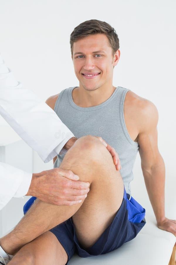 Retrato de um homem novo de sorriso que obtém seu pé examinado imagem de stock royalty free