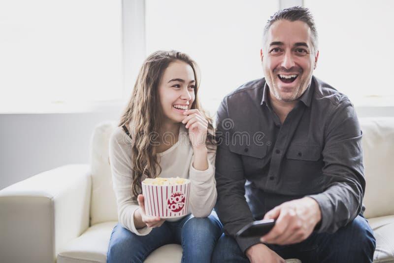 Retrato de um homem novo e de uma filha que olham a tevê ao comer a pipoca no sofá imagens de stock