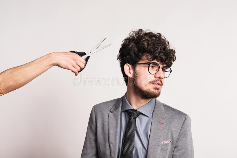 Retrato de um homem novo em um estúdio e de uma mão com tesouras imagens de stock
