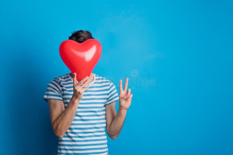 Retrato de um homem novo em um estúdio em um fundo azul, guardando o coração vermelho fotografia de stock royalty free
