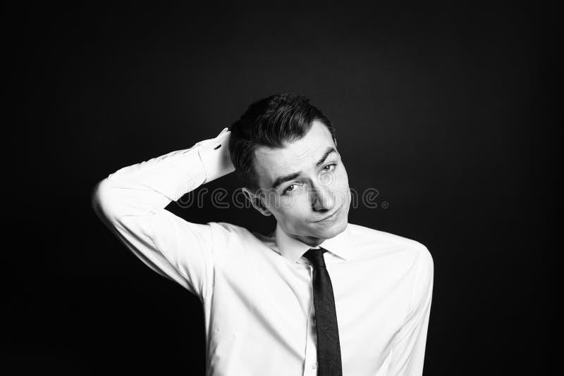 Retrato de um homem novo em uma camisa branca, mão atrás da cabeça imagem de stock