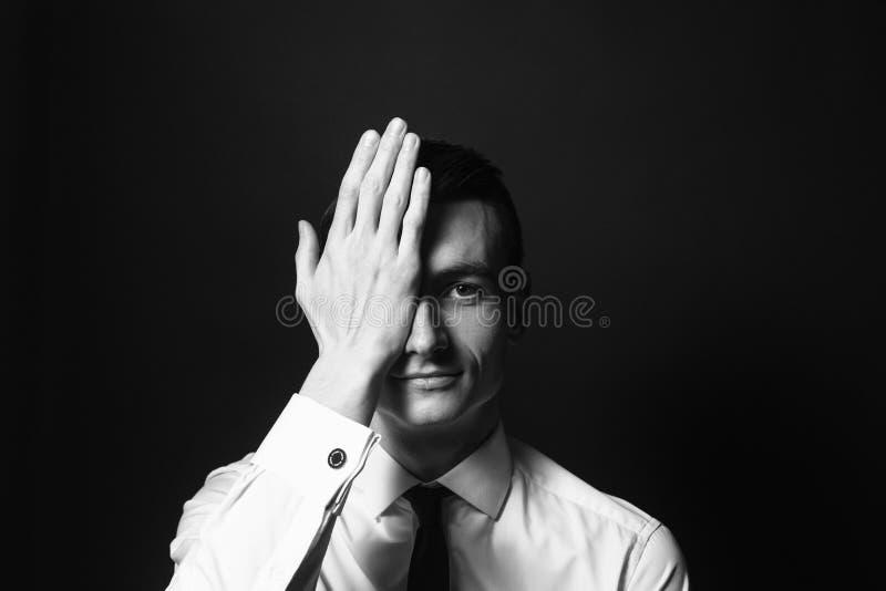 Retrato de um homem novo em uma camisa e em um traje de cerimônia brancos, cov da mão foto de stock royalty free