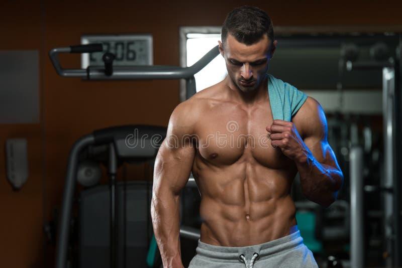 Retrato de um homem novo fisicamente cabido em um clube saudável foto de stock