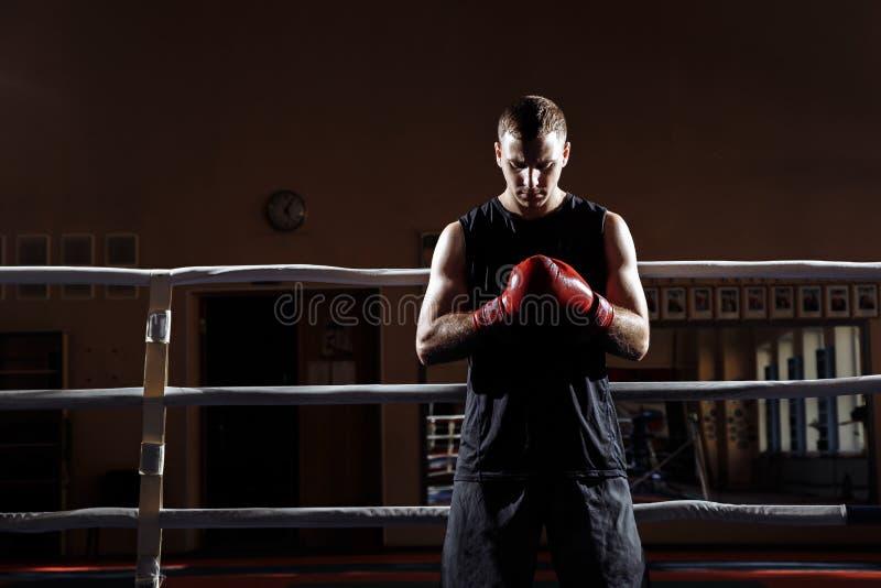 Retrato de um homem novo muscular em luvas de encaixotamento no anel fotografia de stock